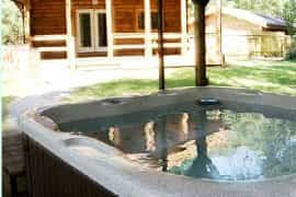 covered hot tub with view to cabin