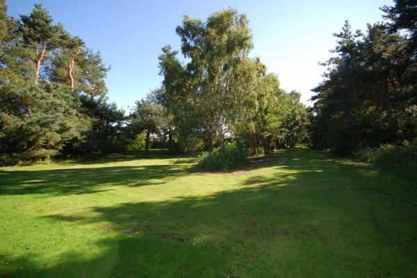 Set in one acre of lawn and woodland