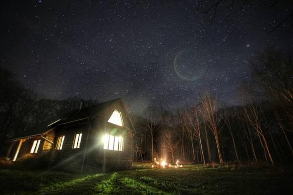 Cruckbarn and firepit at night