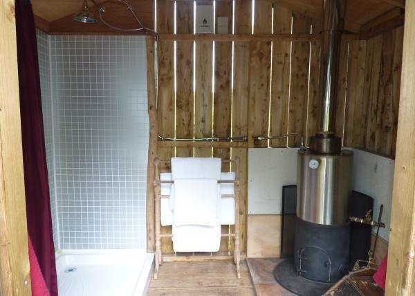 The shower hut at Woodland Camp has a woodburner to heat the water