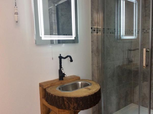 Shower with wooden based sink in communal bathrooms