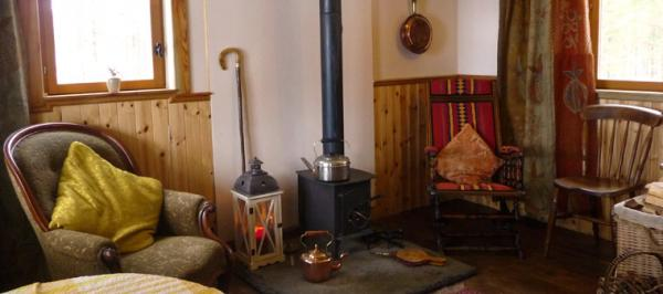 living room and stove in Woodmans Hut